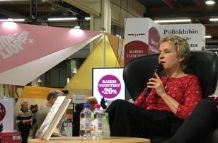kaksi naista nojatuoleissa, toisella mikrofoni, toinen kuuntelee, lava, mainoksia, kirjamessut.