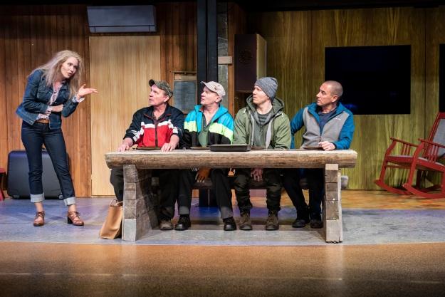 nainen seisoo, neljä miestä istuu pöydän ääressä